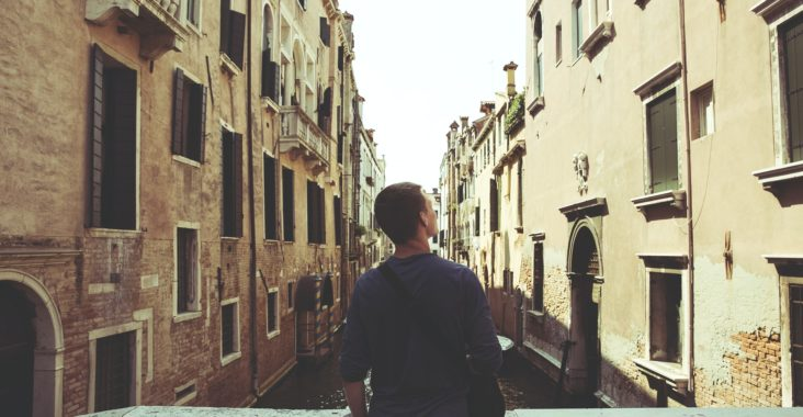 What backpack should I take Interrailing? Man sitting on bridge looking at Venice canal